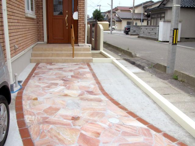 外壁と同系色の敷石で、洗練されたアプローチに